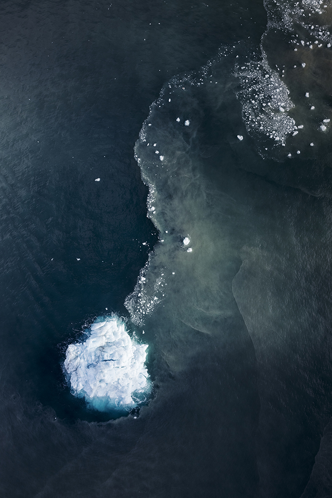 Aerial view of an iceberg and glacier water mixing with salt water in the ocean at Scoresby Sund fjord, east coast of Greenland. 10 percent of the Earth is covered with glacial ice, including glaciers, ice caps, and the ice sheets of Greenland and Antarctica. Glaciers store about 75 percent of the world fresh water and if all land ice melted, sea level would rise approximately 70 meters worldwide.