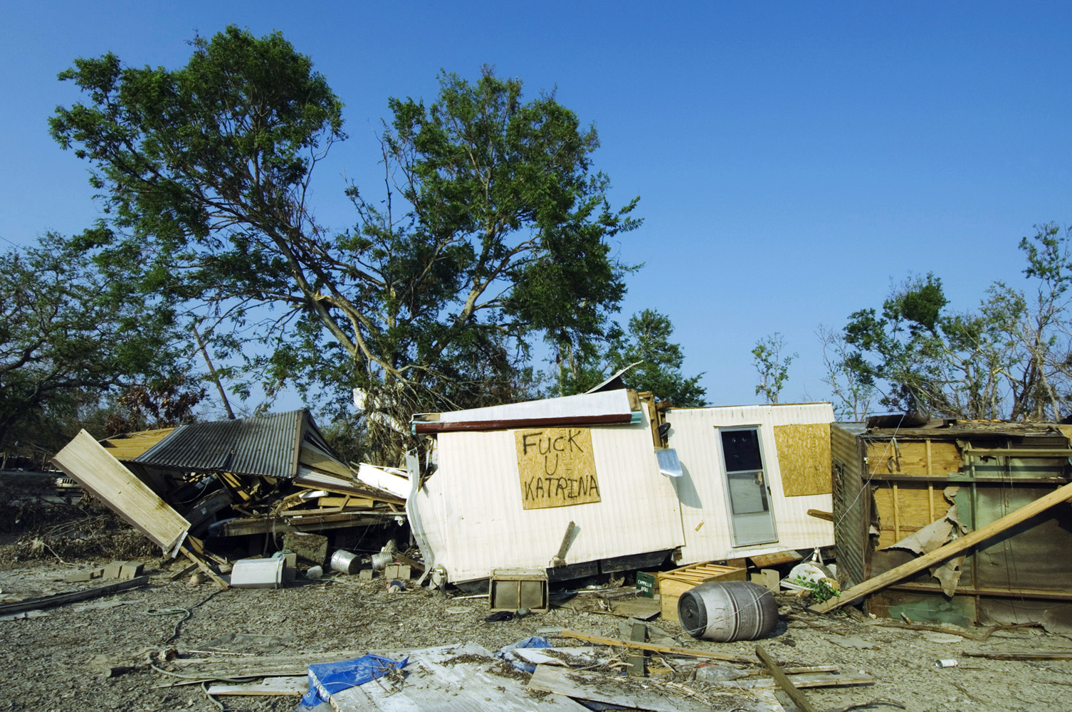 "Plaquemines Parish, Louisiana, USA.Graffitti text ""Fuck You Katrina"" written on the wall of a obliterated mobile home."
