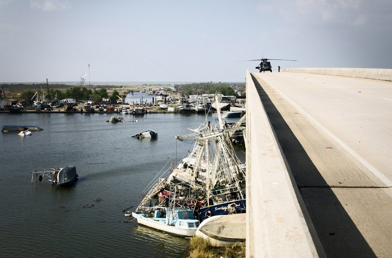 Empire, Plaquemines Parish, Louisiana, USA. Black Hawk helicopter lands on the bridge for surveillance.  Shrimp, Oyster and Menhaden boats thrown around in the harbour of Empire after a 33-foot storm surge accompanying Hurricane Katrina. The entire fishing fleet is wiped out.