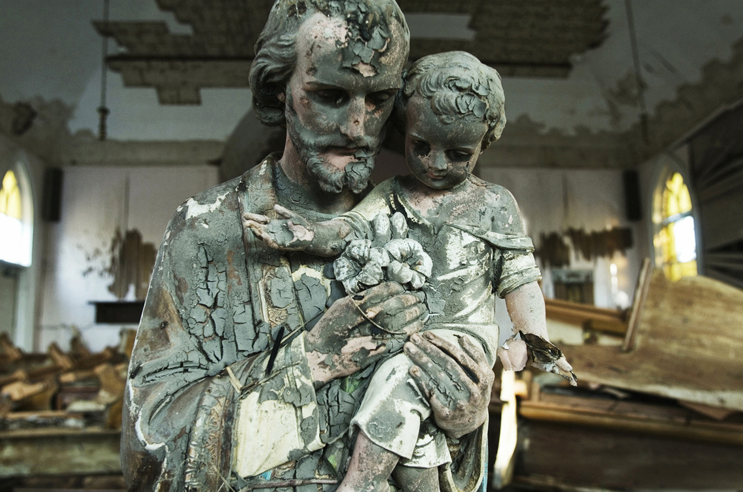 Empire, Plaquemines Parish, Louisiana, USA.  Statue of Jesus covered with mud in the devastated Saint Ann Catholic church of Empire after the 33-foot storm surge accompanying Hurricane Katrina. The church has been lifted of it´s foundations and moved.