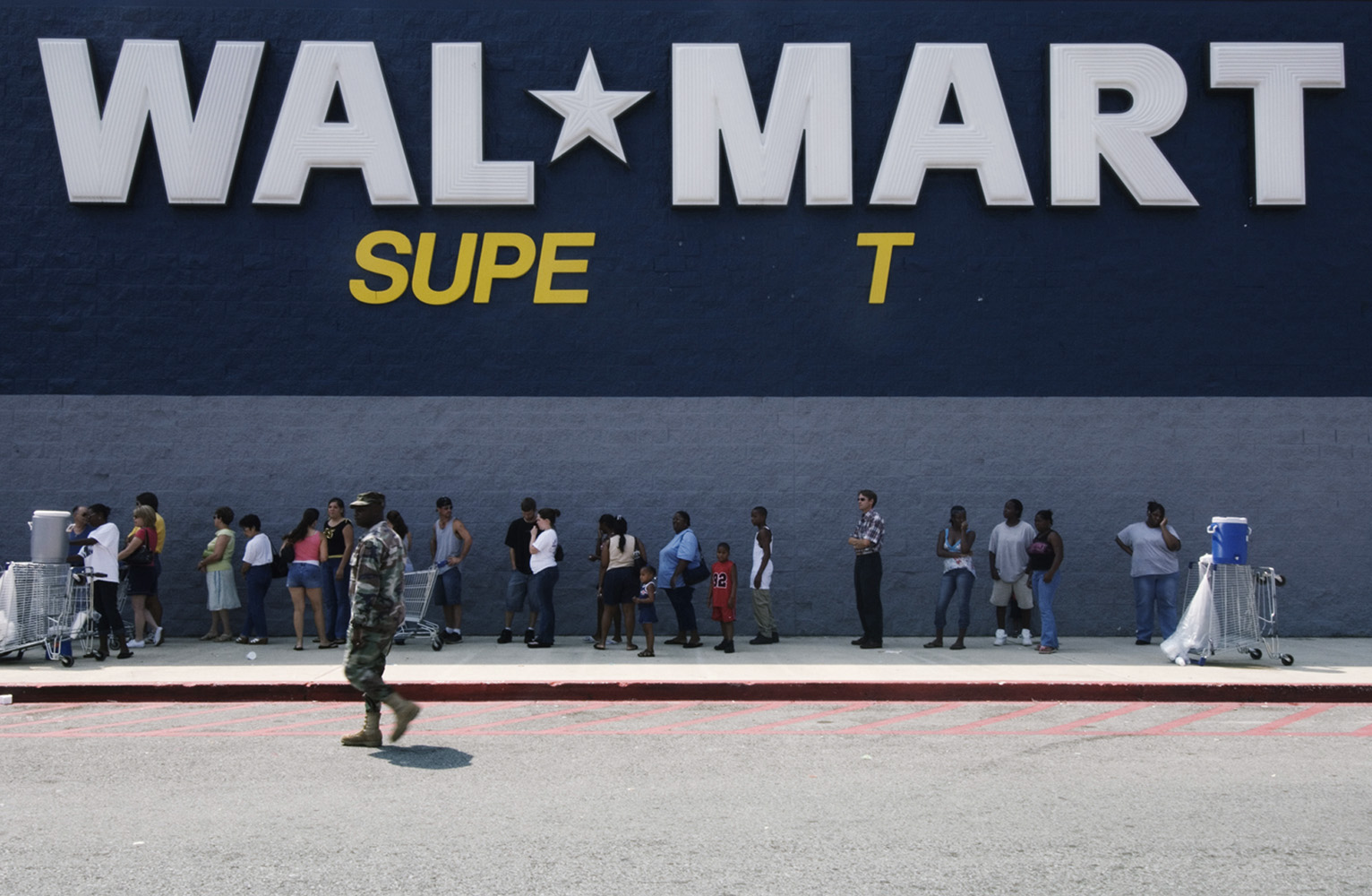 Location: Boutte, community near Orleans, Lousiana, US. A National Guard soldier patrols outside a Wal-Mart store as residents wait to purchase emergency supplies.  Police and soldiers with assault rifles have been guarding the store around the clock.
