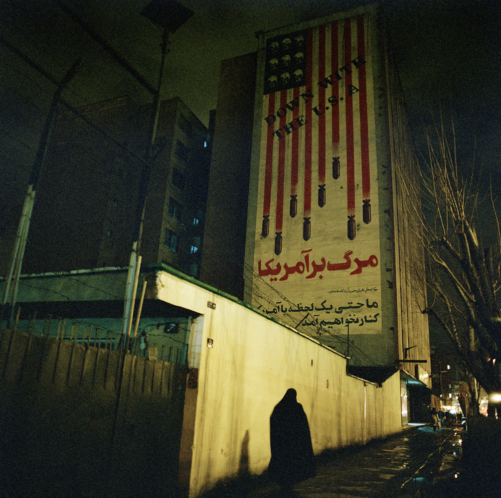 "Mural with the text ""Down with the U.S.A."" located at Karim Khand and Qarani Streets in Tehran. This large-scale mural represents the U.S. flag, in which the red stripes become bombs and the stars turn to skulls. Along with the English text, the Persian inscriptions read: ""Death to America"" and ""Not for a second will we side with America."""
