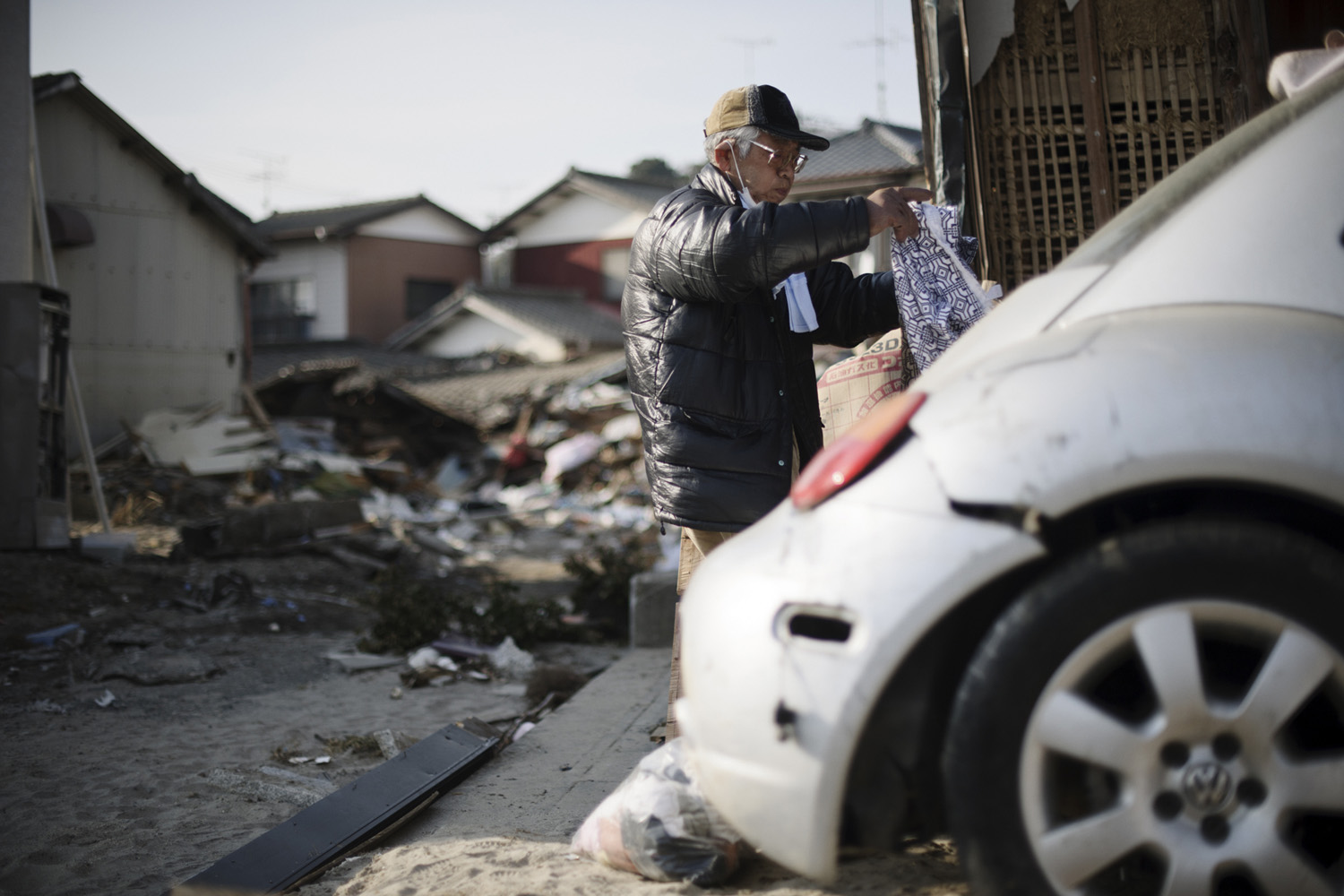 Iwaki City,  Japan, 6 April 2011 - A man sorts through belongings among a destroyed neighbourhood as people begin to return to the Fukushima region to clean up following the Tsunami. In some places, such as Iwaki City, 35 km from the Fukushima Daiichi nuclear plant, the radiation levels are lower as when the biggest leak took place the wind was blowing in the opposite direction. Greenpeace is working in the area to monitor radioactive contamination of food and soil to estimate the health and safety risks for the local population.