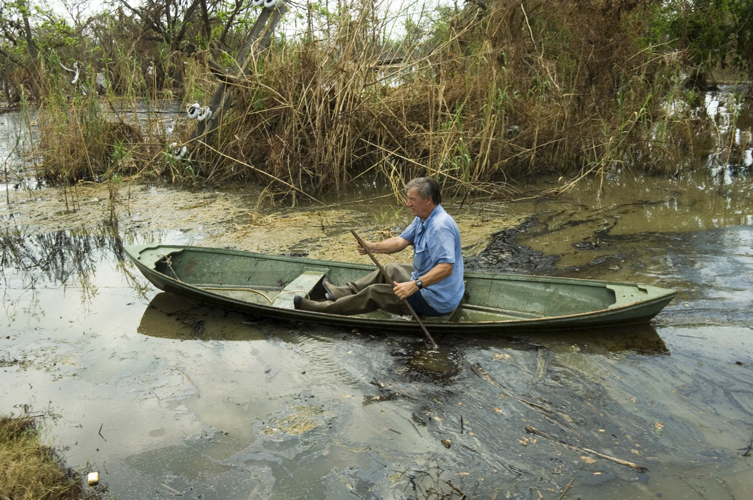 17 September 2005 Empire - Roko Tvrdeic paddles through contaminated water to reach his oyster boat 19 days after Hurricane Katrina hit Plaquemines Parish, southeast of New Orleans. Mr. Tvrdeic emigrated from Croatia 33 years ago and has been farming oysters since.