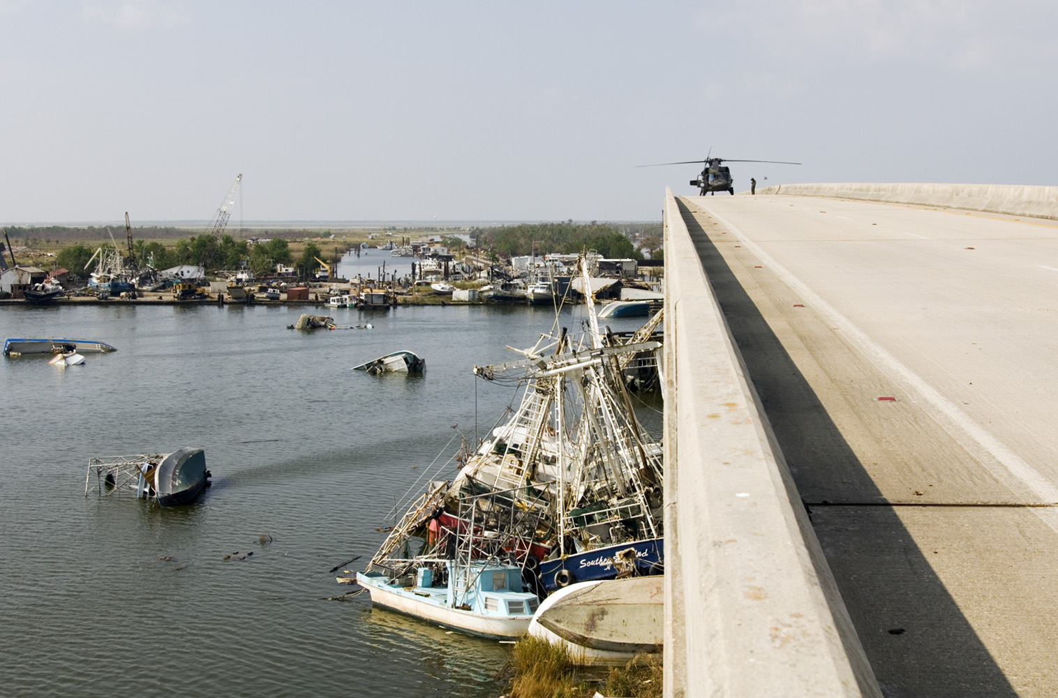 17 September 2005 Empire, Plaquemines Parish, Louisiana, USA. Black Hawk helicopter lands on the bridge for surveillance.  Shrimp, Oyster and Menhaden boats thrown around in the harbour of Empire after a 33-foot storm surge accompanying Hurricane Katrina. The entire fishing fleet is wiped out.