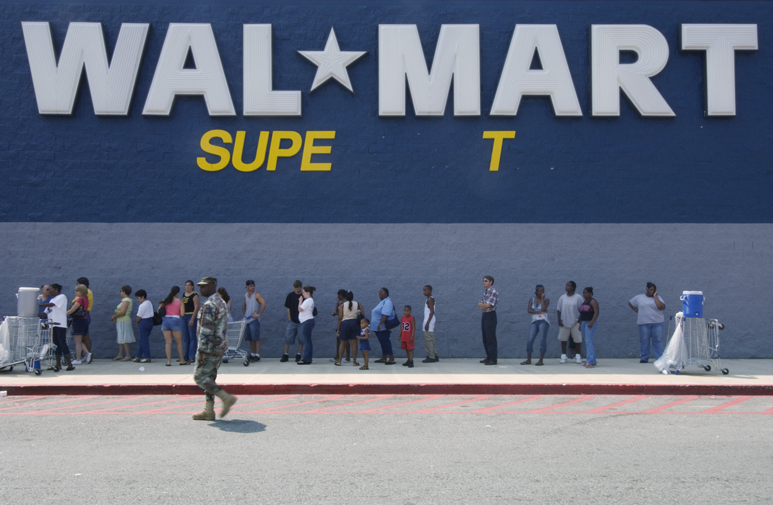 18 September 2005 Location: Boutte, community near Orleans, Lousiana, US. A National Guard soldier patrols outside a Wal-Mart store as residents wait to purchase emergency supplies.  Police and soldiers with assault rifles have been guarding the store around the clock.