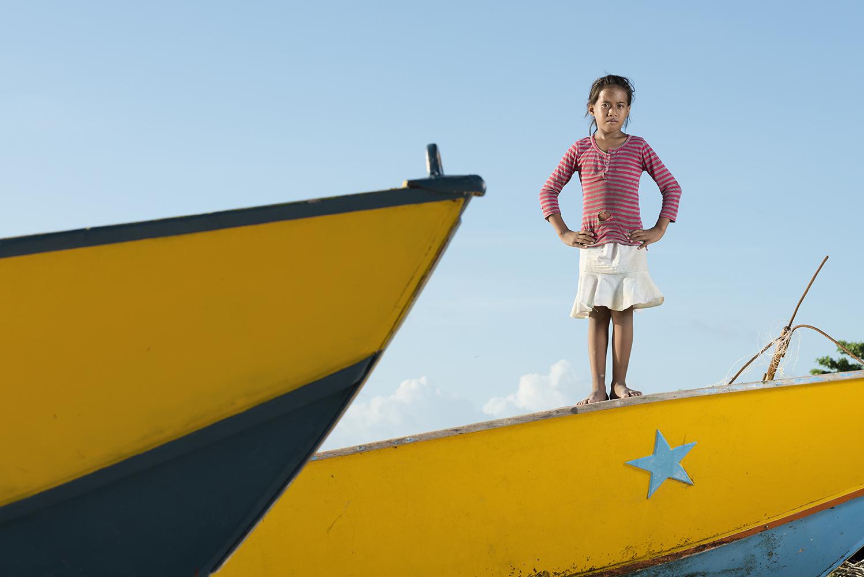 Betio, Tarawa Island, Kiribati, Pacific Ocean Young girl playing on a fishing boat in the village Te O Ni Beeki in Betio, on Tarawa Island, Kiribati