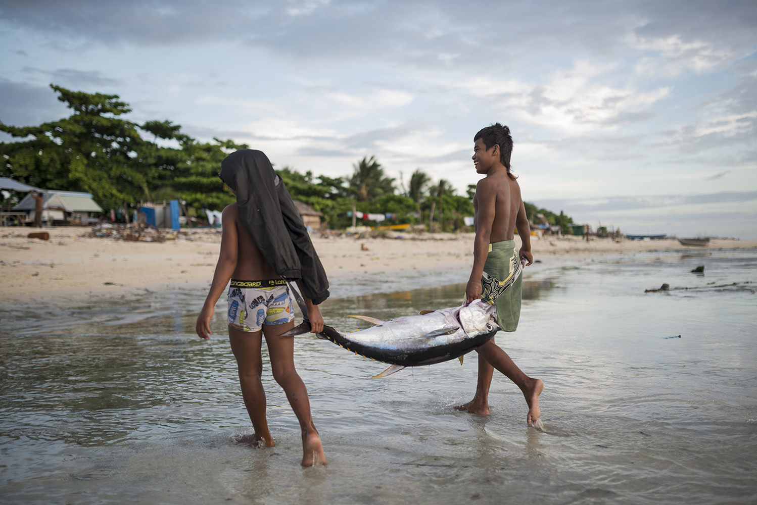Betio, Tarawa Island, Kiribati, Pacific Ocean Young boys in the village Te O Ni Beeki carrying a yellowfin tuna to the shore on Tarawa Island, Kiribati. The nation is considered one of the least developed and poorest countries in the world with people whose livelihoods depend on the fish. Since the arrival of foreign fishing vessels in Kiribati waters the catches for the local fishermen has been reduced.