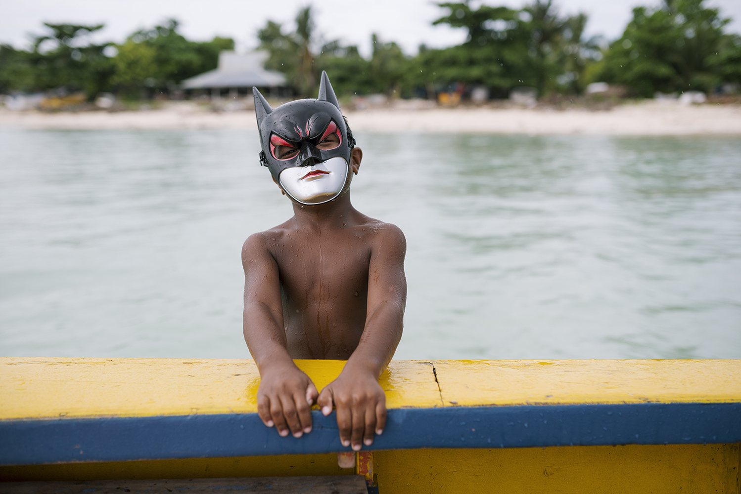 Betio, Tarawa Island, Kiribati, Pacific OceanYoung boy with a batman mask jumping on a artisinal fishing boat in the village Te O Ni Beeki in Betio, on Tarawa Island, Kiribati