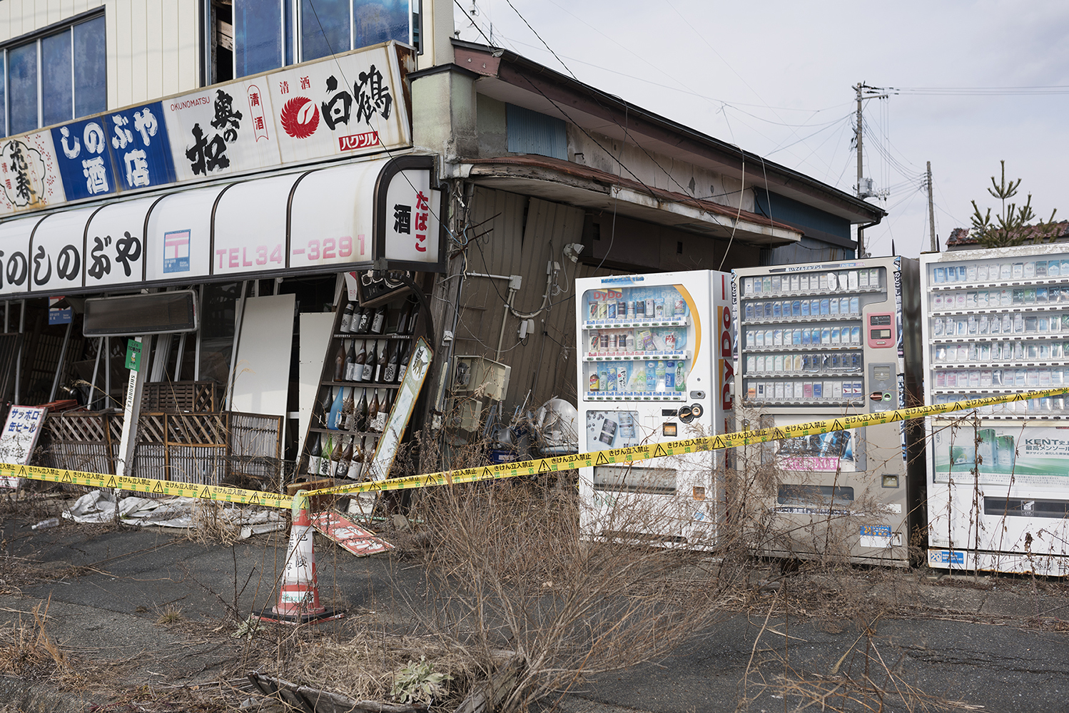 Vending machine and sake bottles outside a store in the abandoned city Namie, located between 5-15 km north of the Fukushima Daiichi Nuclear Power Plant. The city had a population of 18000 people that was evacuated after the disaster. The evacuation area around Fukushima Daiichi is divided in 3 zones. Namie is now on the border of zone 2 and the highest zone 3 where people are not allowed to move back for a long time. Zone 2 is the area that is being prepared for people to return to, as early as 2017 when evacuated citizens will loose their right to the limited compensation they are now receiving. Even after decontamination, most of the area remains dangerously radioactive.According to Greenpeace, it is unacceptable to force the population to return to an area that is still significantly contaminated, even after cleaned up.