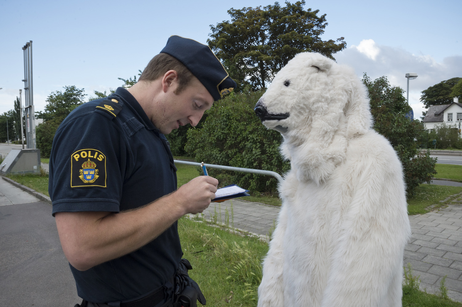 Malmö, Sweden, July 18, 2012. A Greenpeace activist in Polar bear suit being interrogated by the police during a protest at a Shell gas station in Malmoe Sweden. The activist are demonstrating against Shell's plan to drill for oil in the Arctic seas off the coast of Alaska this summer.