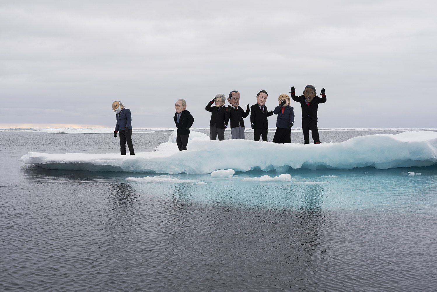 8/9 2014, Svalbard, Norway. Greenpeace activists representing heads of state, wearing suits and papier-mâché heads over drysuits, on an ice floe in the Arctic Ocean northwest of Svalbard. The image is taken during a Greenpeace ship tour, as part of the Save the Arctic campaign, to underline the urgency of climate change most acutely felt in the Arctic, where ice cover is disappearing rapidly, and to urge the global leaders to take urgent action at the climate summit in New York September 23rd for a transition to 100% renewable energy system by mid-century while phasing out fossil fuels. Props made by 