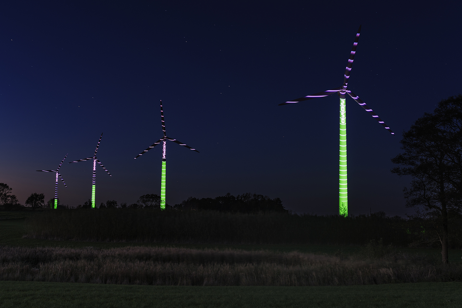 Light projection on wind turbines showing the Danish roadmap to 100% renewable energy, from 2010 to 2050. Renewable energy is a key solution to climate change, says the IPCC, currently meeting in Copenhagen, Denmark.