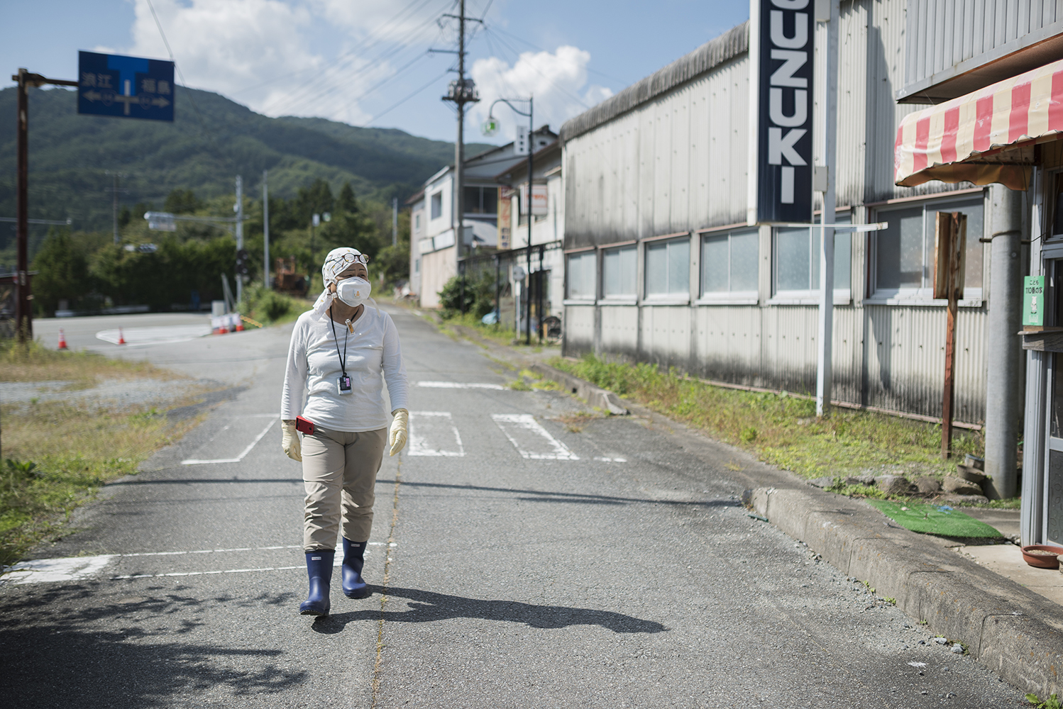 Evacuee and Fukushima survivor, Mrs Kanno walking through the empty streets of Tsushima, inside the highly contaminated exclusion zone of Namie, Fukushima prefecture. This area is closed for people to return to, however, the Japanese government plans to open a small area of Tsushima as early as 2023. The levels of radiation measured by Greenpeace in this highly contaminated area mean that it will be many decades and beyond the end of the century before radiation levels will even approach government targets.