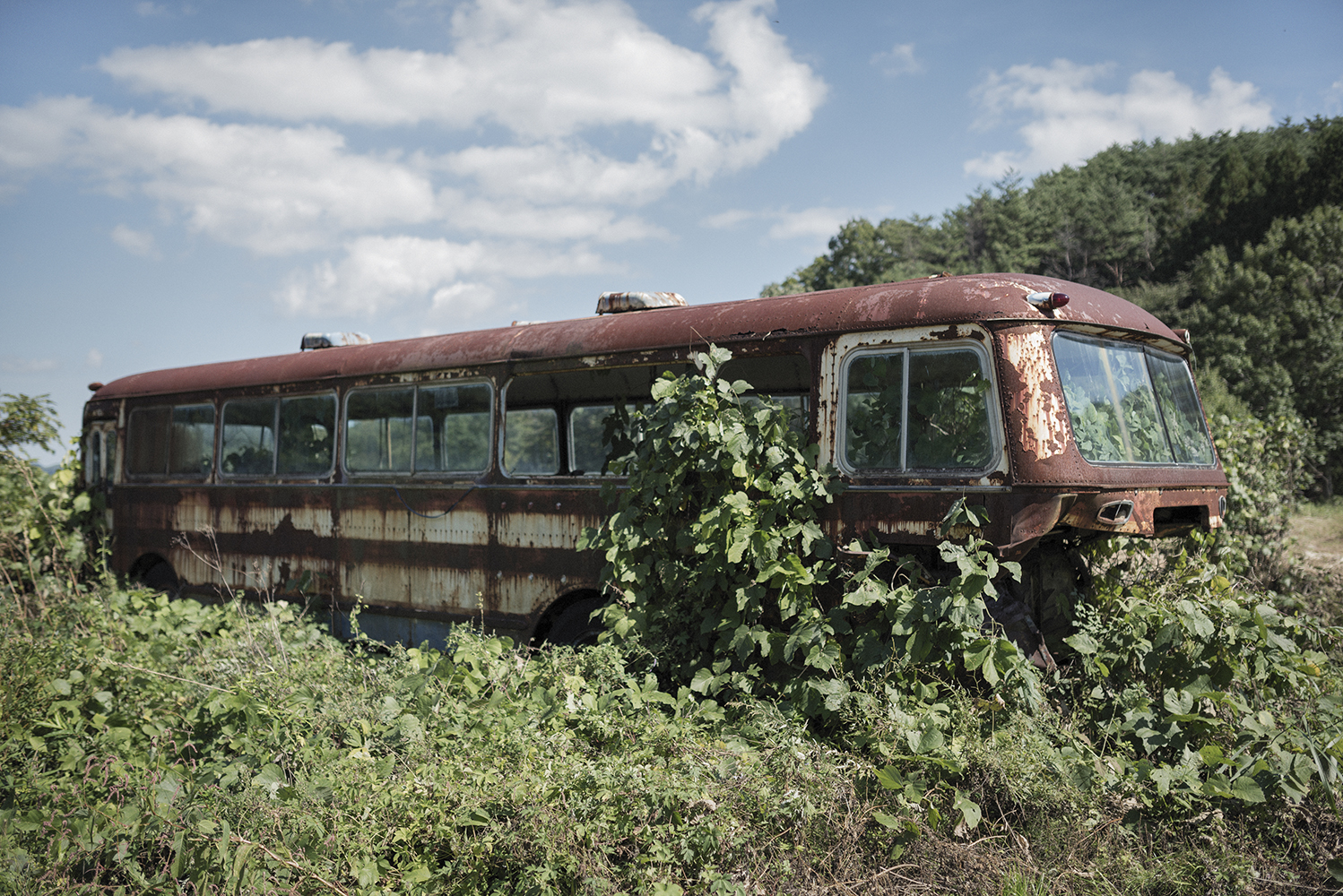 Iitate, Fukushima prefecture.Abandoned bus outside former resident of Iitate Toru Anzai's house in Fukushima prefecture. The house, which is approximately 32 km northwest of the Fukushima Daiichi nuclear plant, was heavily exposed to radioactive fallout in March 2011. The Government lifted evacuation orders for a part of Iitate in March 2017 despite radiation readings that mean it is not safe for people to return to Iitate. As of December 2017, the population of Iitate was 505, 7.7% of the population in March 2011. Greenpeace has been conducting radiation surveys in Iitate since March 2011, when it was the first to warn of the high levels of radiation and the urgent need to evacuate.