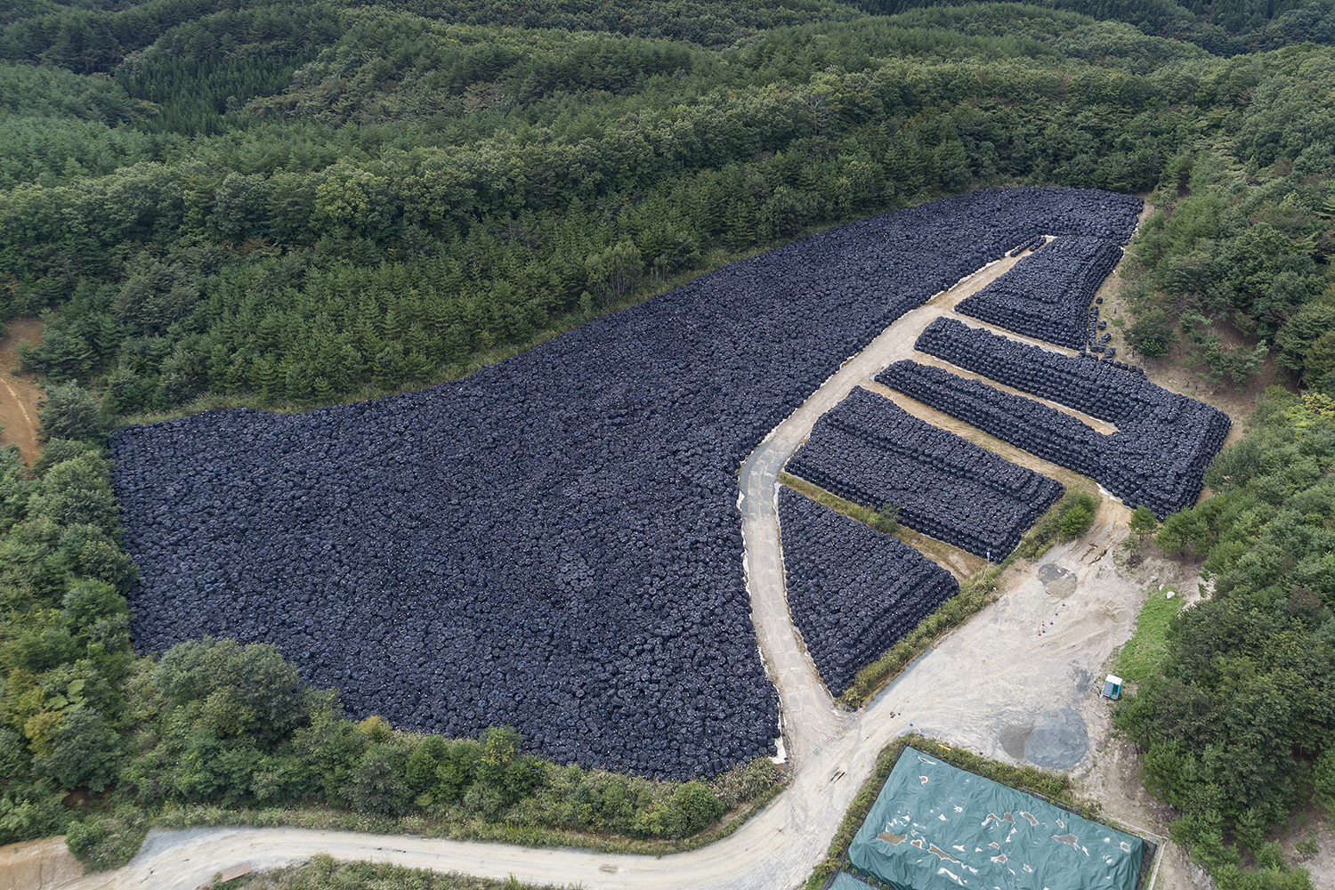 Aerial view of nuclear waste storage area in the mountainous forests of Iitate, Fukushima prefecture in Japan. Adopting a return to normal policy, the Japanese government undertook an unprecedented decontamination program for areas of Fukushima contaminated by the tripe reactor meltdown in March 2011. Fukushima prefecture is 70 percent mountainous forest which has not and cannot be decontaminated, with decontamination efforts focused along roads and in towns, farmland and in narrow areas around people's houses. Even so, the result has been that the Japanese authorities have produced a nuclear waste crisis, with over 13 million cubic meters of waste located in 147,000 locations (as of July 2017). The Japanese government is determined to force people back to their homes despite the on-going radiation risks and the vast volumes of nuclear waste.
