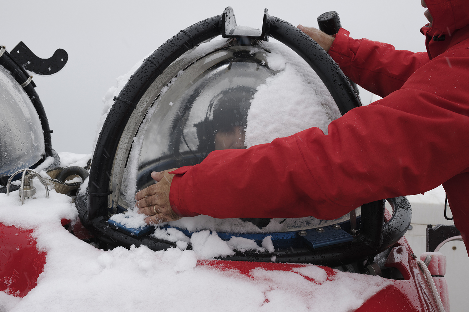 A submersible technichian wiping away the snow from the cockpit for submarine pilot John Hocevar sitting in a two person submarine about to be launched from Greenpeace ship the Arctic Sunrise. Greenpeace is conducting submarine-based scientific research to strengthen the proposal to create the largest protected area on the planet, an Antarctic Ocean Sanctuary.