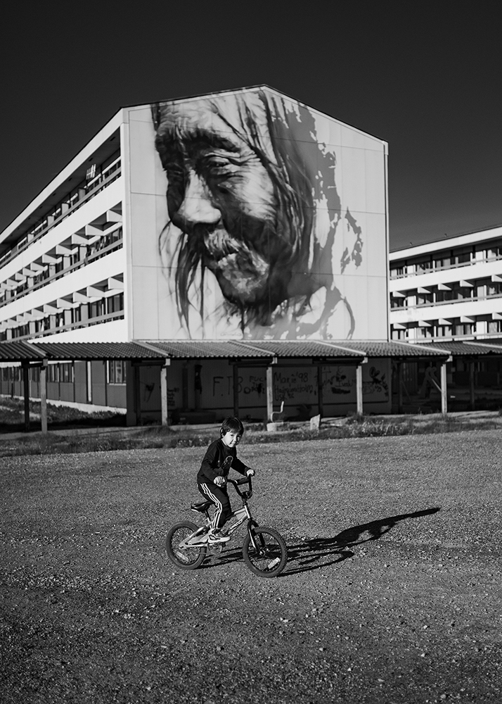 "Kid bicycling in front of the mural ""Pooŋojorteq"", a portrait of a Greenlandic hunter painted by the Australian artist Guido Van Helte, in the capital town Nuuk on Greenland. The painting is located on Blok 5, of the housing Bloks in Nuuk, built in the 1950's in an attempt by the Danish government to modernise the Greenlandic society and its Inuit population. Through the closing down of social services in the remote settlements a proud hunter society was forcibly moved into these urban Blok's to work industrial jobs in the city. This rapid change over one generation resulted in high rates of suicide, alcoholism and many other social problems."