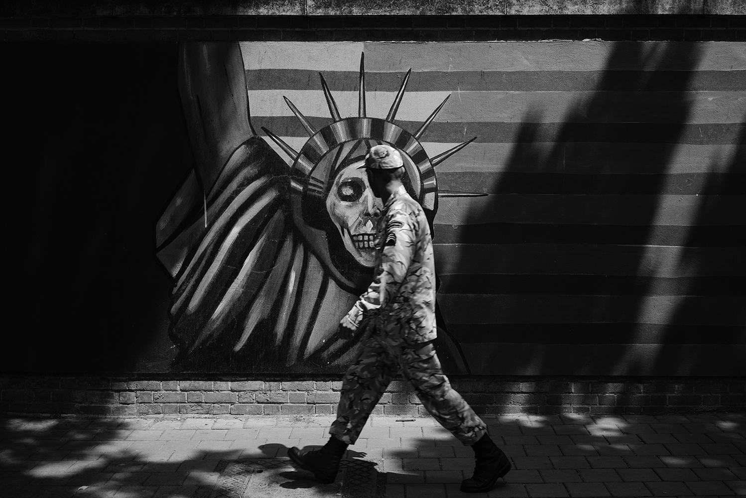 Iranian soldier looking at the Anti-American propaganda mural with an interpretation of the Statue of Liberty, at the former US Embassy 'Den of Espionage', on Talaqani Street in Tehran.  The former US embassy is where the 1953 coup that brought down Mohammad Mossadegh was orchestrated. During the Islamic revolution 1979, students who feared a repeat coup stormed the embassy and held 52 diplomats hostage for 444 days.