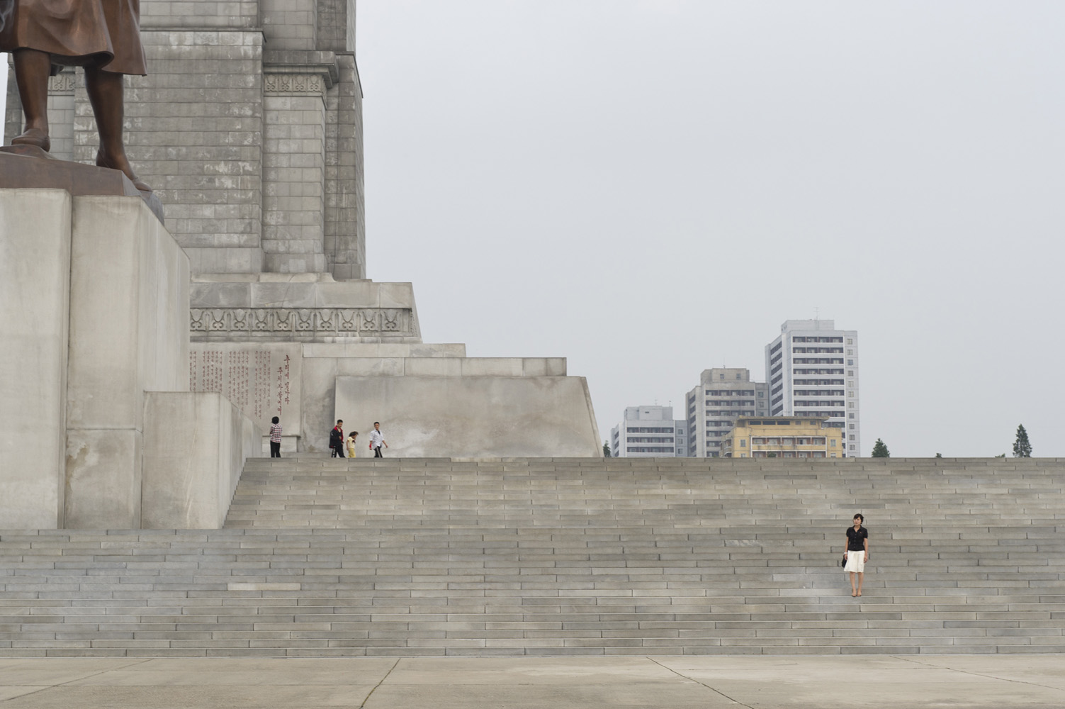 North Korean woman standing at the stairs of the tower of the Juche Idea, a 170-meter tall monument.  It is presumed to be modeled on the Washington Monument, which it surpasses in height by less than a metre.