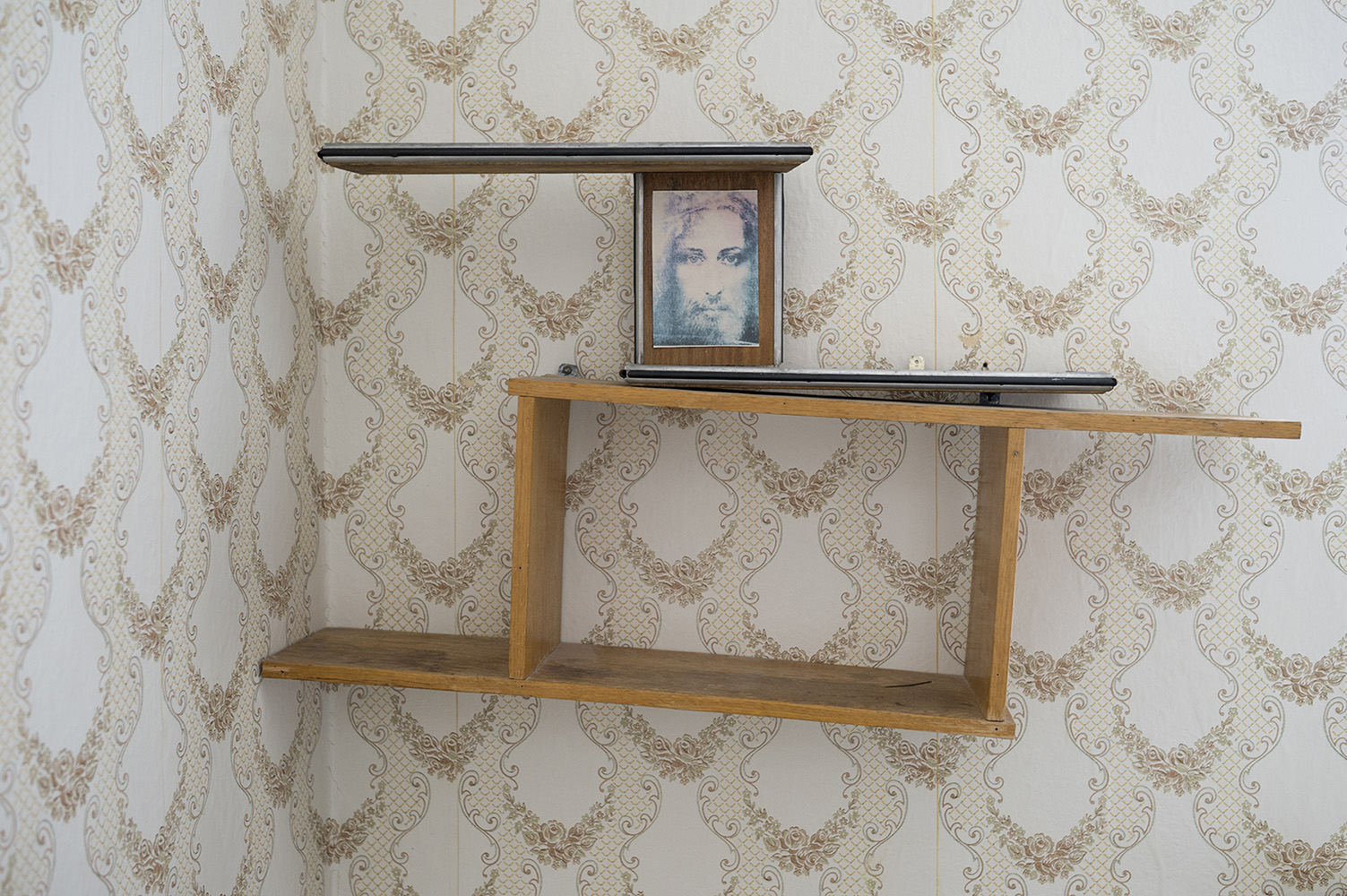 Vintage wallpaper and slanted shelves in the workers' housing in Pyramiden.Pyramiden is a Russian settlement and coal mining community on the archipelago of Svalbard, Norway. Founded by Sweden in 1910 and sold to the Soviet Union in 1927, Pyramiden was closed in 1998 and has since remained largely abandoned with most of its infrastructure and buildings still in place.
