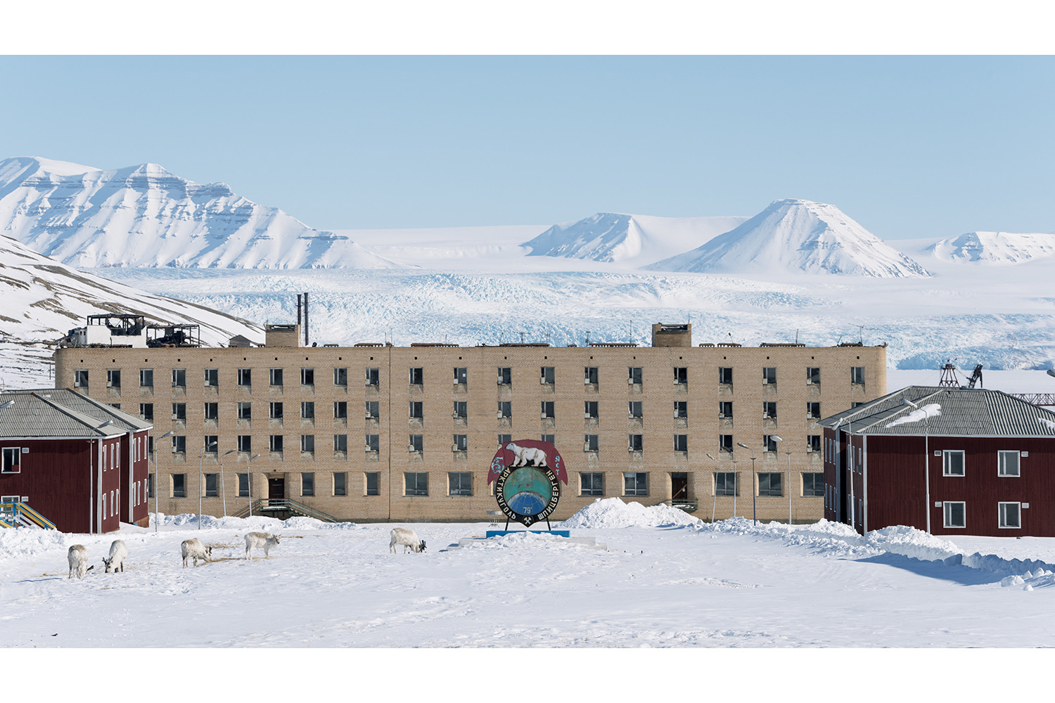 Pyramiden Ghost Town on Svalbard. Reindeer graze with Nordendkioldbreen Glacier in the background.Pyramiden is a Russian settlement and coal mining community on the archipelago of Svalbard, Norway. Founded by Sweden in 1910 and sold to the Soviet Union in 1927, Pyramiden was closed in 1998 and has since remained largely abandoned with most of its infrastructure and buildings still in place.