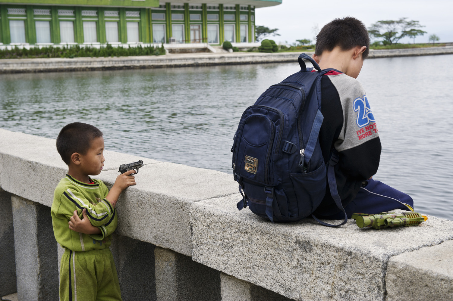 Kid playing with a toy gun in the harbour of Wŏnsan, North Korea.