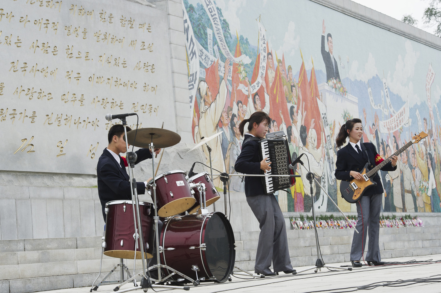 Live music on the national day in North Korea, with a band playing in front of a Communist propaganda bulletin board.
