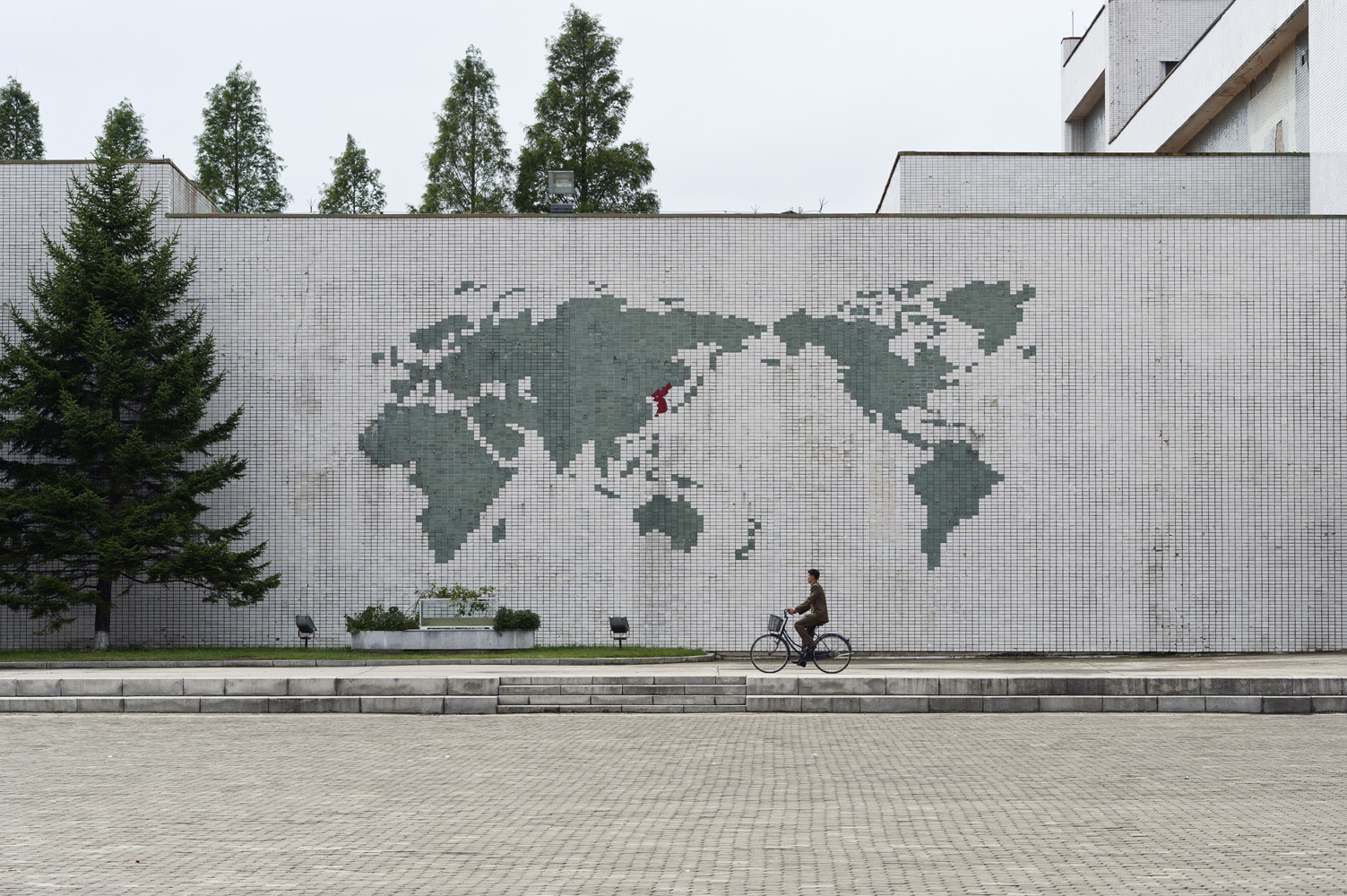 Man bicycling under a world map mural at Songdowon International Children's Union Camp in Wŏnsan, Kangwŏn Province.