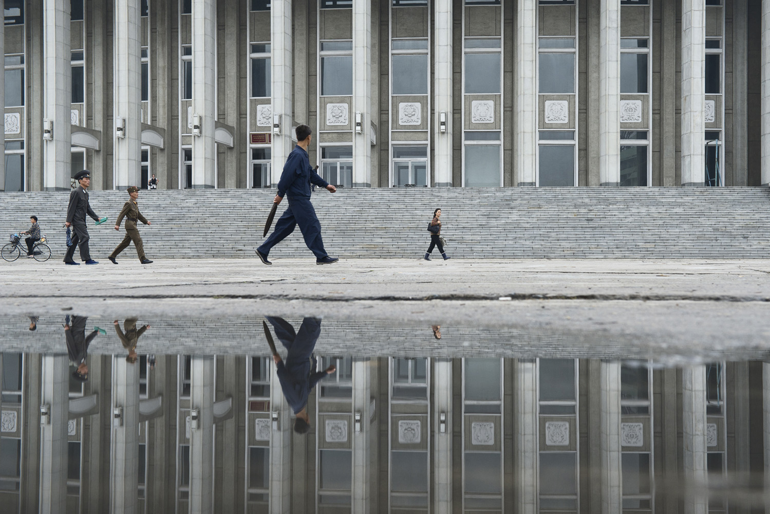 Reflection of people walking outside Hamhung Grand Theatre. Hamhŭng is an important chemical industry center in the DPRK. It is an industrial city which serves as a major port for North Korean foreign trade. Production includes textiles (particularly vinalon), metalware, machinery, refined oil and processed food. It is also said to be North Korea's largest center of methamphetamine production both for export and illicitly for internal consumption.