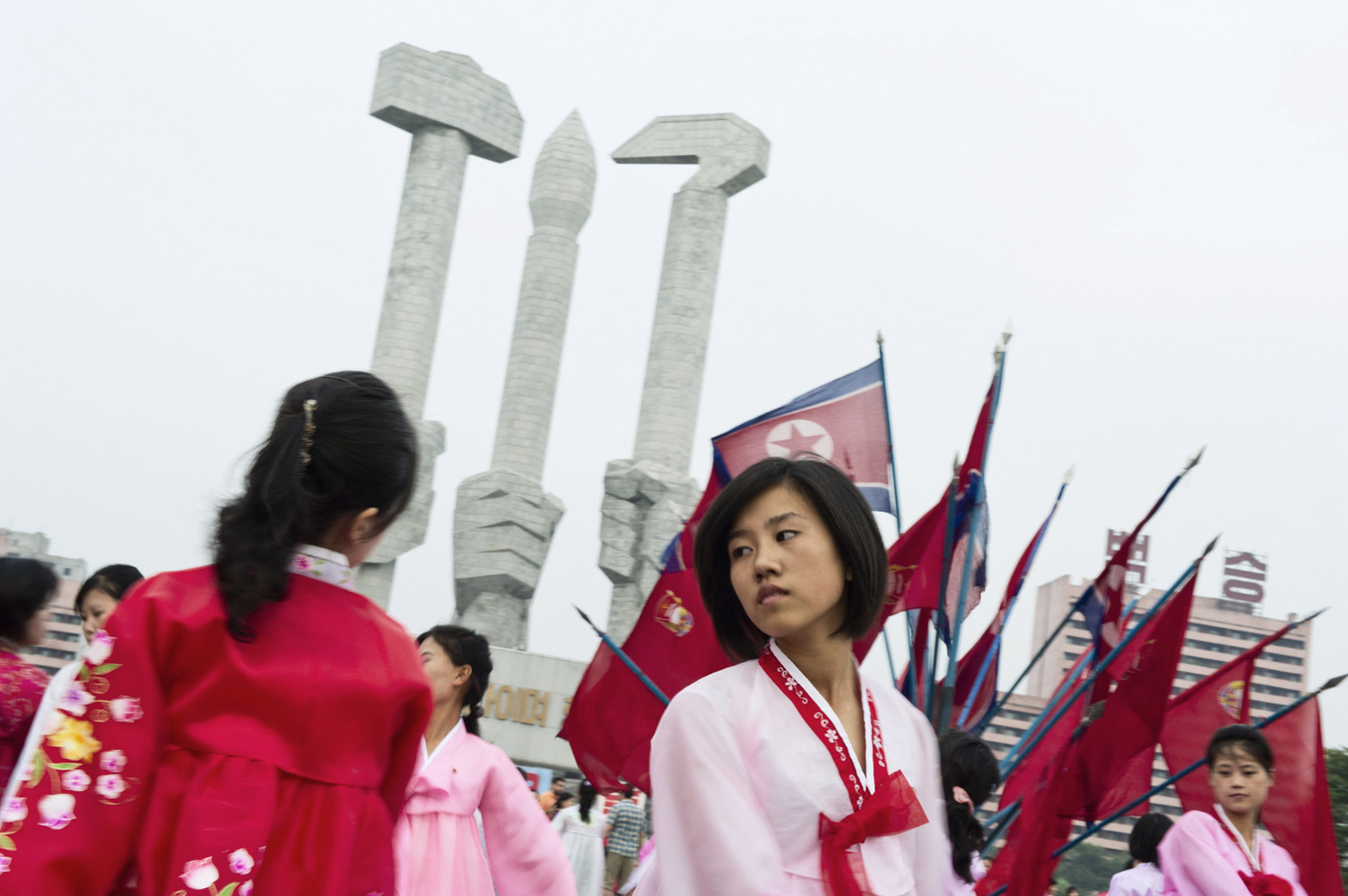 Young Koreans dancing in front of a Monument, Workers' Party of Korea (sickle, hammer and brush), on the national day.