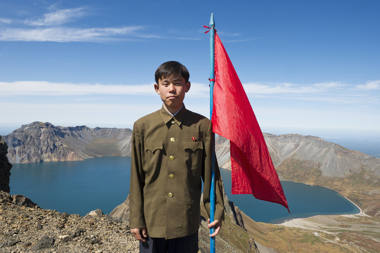 North Korean student holding a red flag on top of the volcanic mountain Baekdu (2744 m above sea level), the highest mountain in North Korea, with Chon Crater Lake in the background.  Kim Jong-il's official biography states that he was born in a secret military camp on Baekdu Mountain. Dense forest around the mountain provided bases for Korean armed resistance against the Japanese occupation, and later communist guerrillas during the Korean War. The Baekdu Mountain has been worshipped by the surrounding peoples throughout history. Both the Koreans and Manchus consider it the place of their ancestral origin.